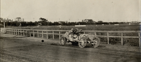 View of driver racing Zust car no. 15 on track during 1908 Brighton Beach races in New York. Handwritten on back: